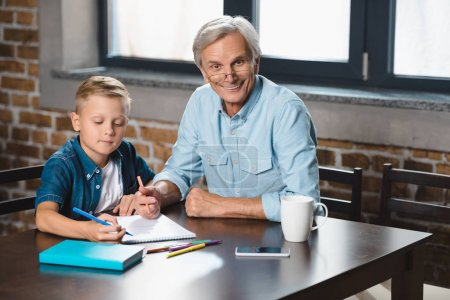 grandfather and grandson drawing together