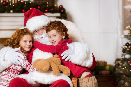 Photo for Portrait of smiling kids hugging santa claus at home - Royalty Free Image