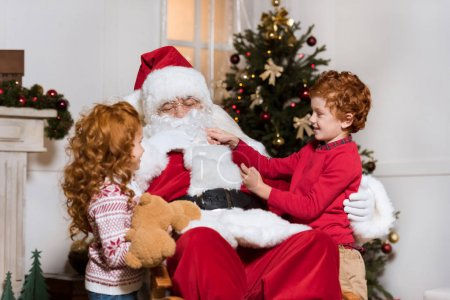 Photo for Portrait of little kids playing together with santa claus at home - Royalty Free Image