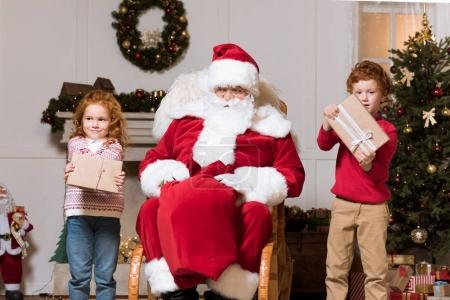 santa claus and children with presents