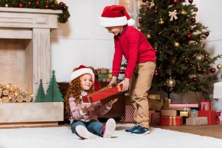 kids in santa claus hats with gift