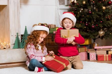 kids in santa claus hats with gifts