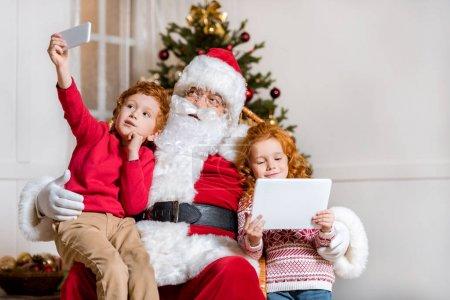 Photo pour Portrait de petit garçon prenant selfie avec Père Noël claus tandis que sœur en utilisant tablette à la maison - image libre de droit