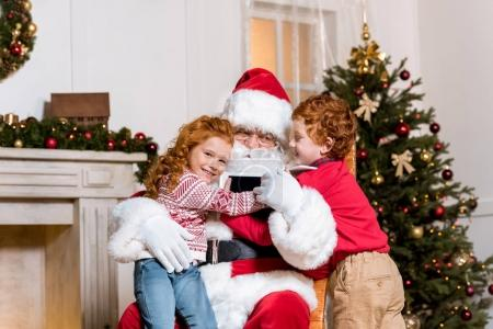 Photo for Portrait of children with digital devices hugging santa claus in rolling chair - Royalty Free Image