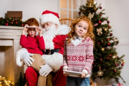 santa claus and children with digital devices