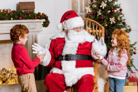kids giving milk and cookie to santa