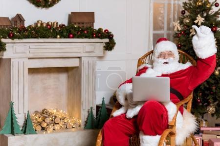 Photo pour Santa claus avec ordinateur portable montrant pouce vers le haut tout en se reposant sur rocking chair à la maison - image libre de droit