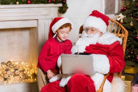 Photo pour Santa claus et petit garçon dans santa claus chapeau en utilisant ordinateur portable ensemble à la maison - image libre de droit