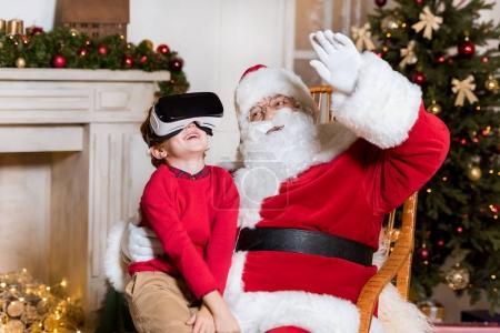 Photo pour Petit garçon dans vr casque assis sur les genoux du Père Noël claus - image libre de droit