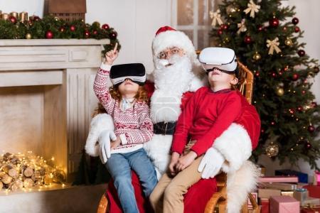 Photo pour Enfants dans des casques vr assis sur les genoux du Père Noël à la maison - image libre de droit