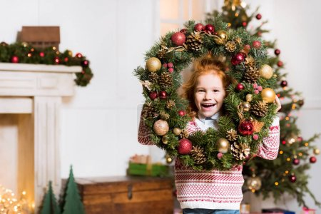 Photo pour Portrait de heureuse petite fille avec couronne de Noël regardant la caméra - image libre de droit