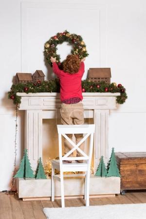 Photo pour Vue arrière de l'enfant debout sur la chaise et suspendue couronne de Noël sous la cheminée à la maison - image libre de droit