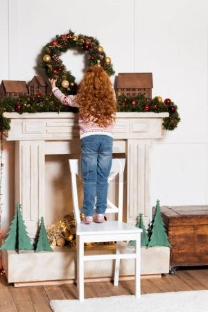 Child hanging christmas wreath at home