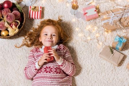 Kid lying on floor with gifts