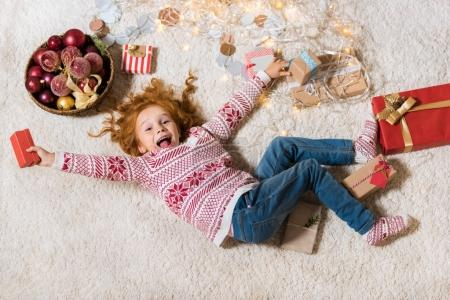 kid lying on floor with gifts