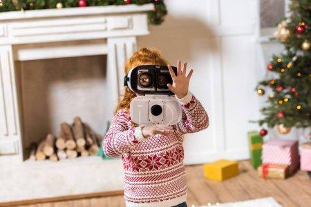 Photo pour Portrait de petite fille jouant dans le casque de réalité virtuelle à la maison - image libre de droit