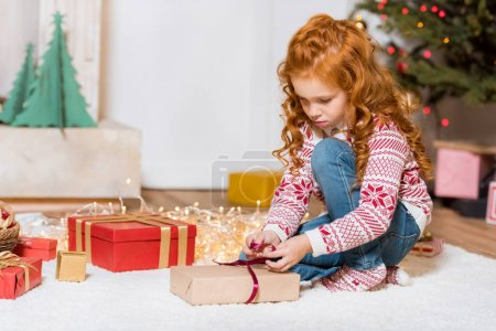 child unpacking christmas gift