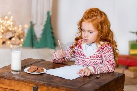 child writing wish list to santa