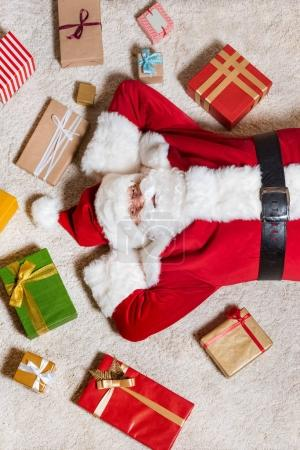 santa claus lying on floor with presents