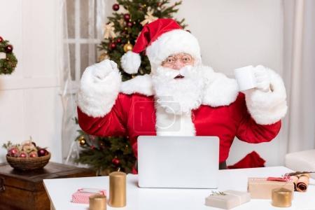 Photo pour Portrait de Père Noël excité claus avec ordinateur portable sur la table regardant la caméra à la maison - image libre de droit