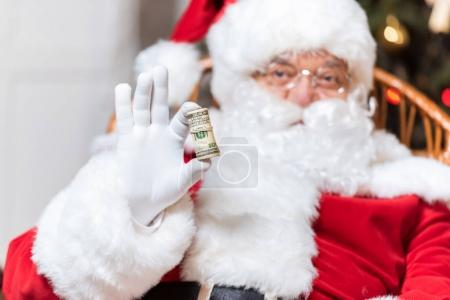 Photo for Portrait of santa claus showing roll of money in hand - Royalty Free Image