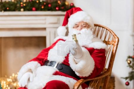 Photo for Portrait of santa claus holding roll of money in hand - Royalty Free Image