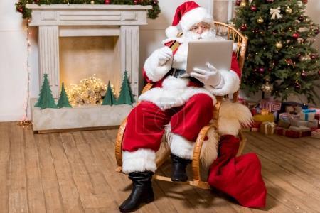 Photo pour Santa claus avec carte de crédit et ordinateur portable shopping en ligne à la maison - image libre de droit