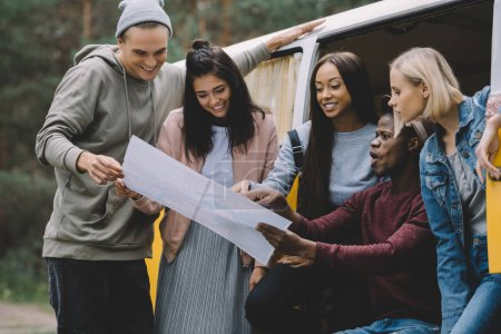 Photo pour Jeunes amis multiethniques regardant la carte tout en voyageant en minivan rétro - image libre de droit