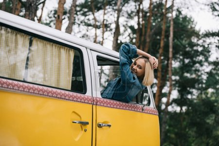 Photo for Happy attractive blonde girl sitting in retro styled minivan - Royalty Free Image