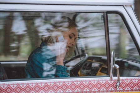 Photo for Young girl using smartphone while sitting in retro styled minivan - Royalty Free Image