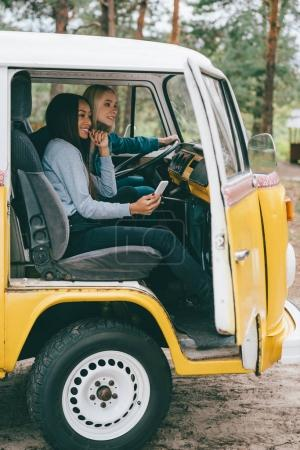 Photo for Multiethnic girls using smartphone while sitting in retro minivan - Royalty Free Image