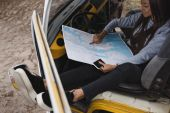 girl with smartphone and map in minivan