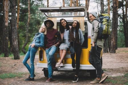 multiethnic travelers near minivan in forest
