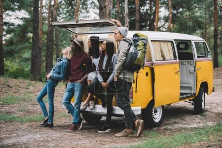 Photo for Young multiethnic travelers posing together near retro minivan in forest - Royalty Free Image