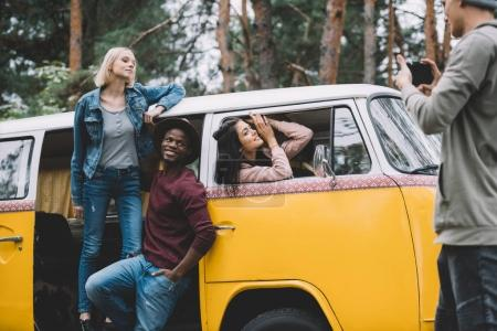 Photo for Young multiethnic friends taking photo at camera near retro minivan in forest - Royalty Free Image