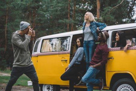 Photo pour Jeunes amis multiethniques prenant des photos à la caméra près de minifourgonnette rétro dans la forêt - image libre de droit