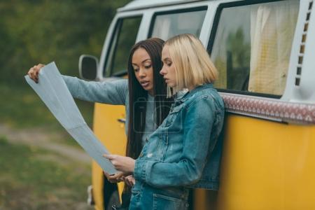 Photo pour Filles multiethniques regardant la carte et debout à minivan rétro - image libre de droit
