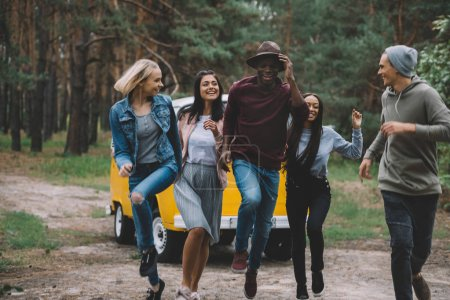 Photo for Young multiethnic friends jumping and having fun together by retro minivan in forest - Royalty Free Image