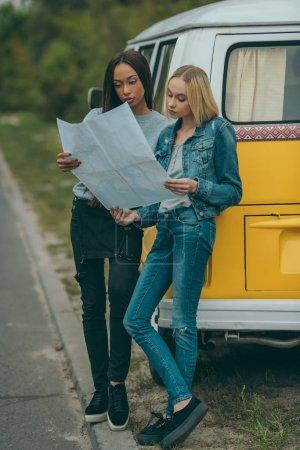 Photo pour Attrayant amis multiethniques regardant la carte et debout à minivan rétro - image libre de droit