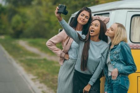 Photo pour Excité amis multiethniques prendre selfie à la caméra tout en se tenant debout à minivan rétro - image libre de droit