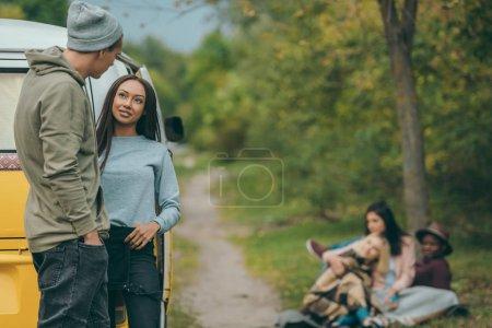 Photo pour L'heureux couple interracial se tenant à minivan rétro avec des amis derrière - image libre de droit