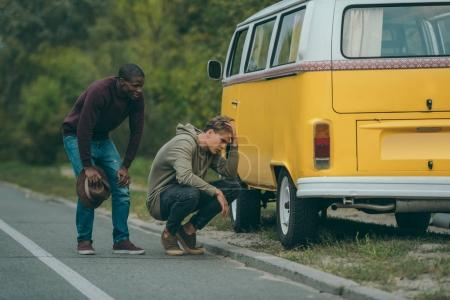 multiethnic men near broken minivan