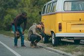 multiethnic men near broken minivan