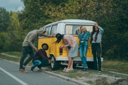 Photo for Multiethnic friends standing near broken minivan on road - Royalty Free Image