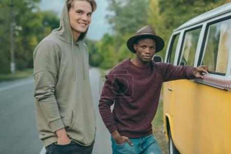 multiethnic men standing at minivan