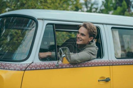 Photo pour Beau jeune homme souriant conduite minifourgonnette rétro - image libre de droit