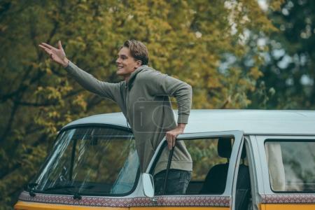 Photo pour Beau jeune homme souriant gestuelle en minifourgonnette rétro - image libre de droit