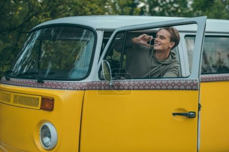 Man using smartphone in minivan