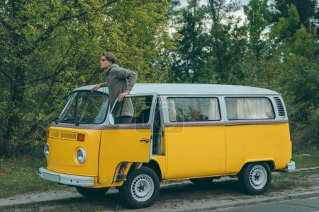 Photo for Handsome young traveler in retro minivan looking away - Royalty Free Image