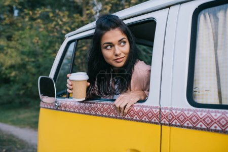 Traveler with coffee in minivan